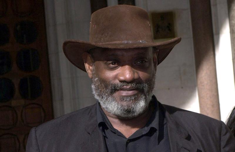 FILE - In this March 3, 2000 file photo, author and broadcaster Darcus Howe walks, in London. The biographer of British black activist Howe says he has died. He was 74 and had been suffering from prostate cancer, it was reported on Sunday, April 2, 2017. (Stefan Rousseau/PA via AP, File)