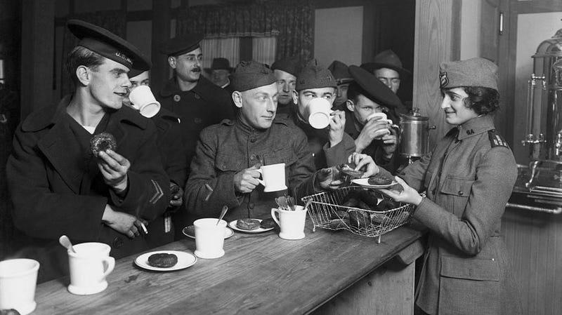 Black and white photo of navy sailors lining up to receive coffee and doughnuts