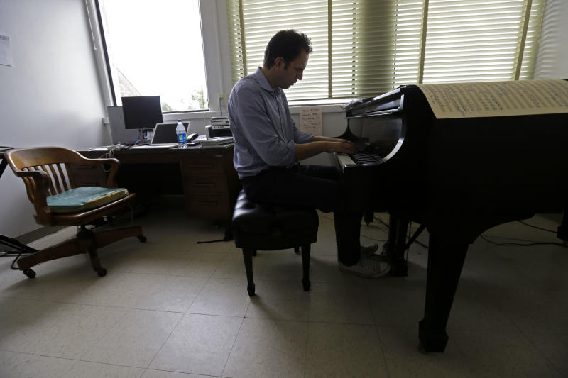 "Yotam Haber plays the piano while working on the finishing touches of his composition ""A More Convenient Season"" in his office at the University of New Orleans on Thursday, Sept. 5, 2013. Rather than focus in a literal way on the Sept. 15, 1963, Ku Klux Klan bombing that killed four little black girls on their way to Sunday school, the Dutch-born composer sought to evoke Birmingham's role in the larger civil rights struggle. ""I'm not telling Birmingham her own story,"" says Haber, whose work is scheduled to premiere at the University of Alabama on Sept. 21, 2013. ""She knows it far better than I will ever be able to tell it."" (AP Photo/Gerald Herbert)"