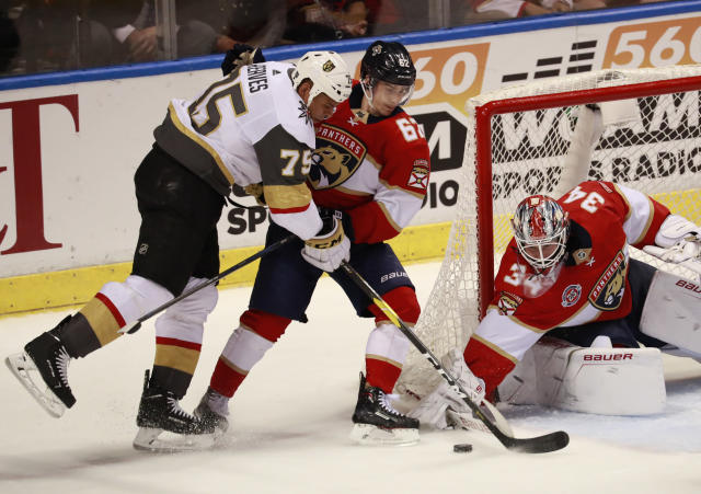 Vegas Golden Knights right wing Ryan Reaves (75) attempts to shoot at Florida Panthers goaltender James Reimer (34) and center Denis Malgin (62) during the second period of an NHL hockey game, Saturday, Feb. 2, 2019 in Sunrise, Fla. (AP Photo/Wilfredo Lee)