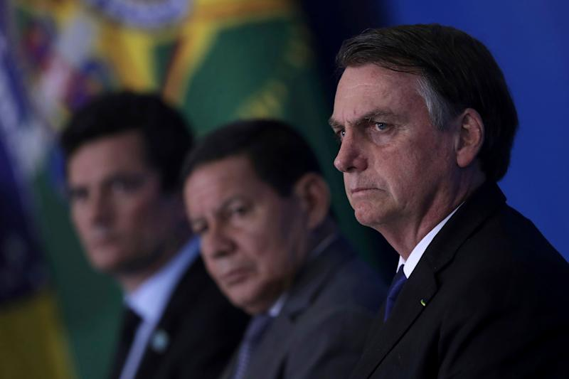 Brazil's President Jair Bolsonaro attends a ceremony where he signed a second decree that eases gun restrictions, during the signing ceremony at Planalto presidential palace in Brasilia, Brazil, Tuesday, May 7, 2019. The decree opens Brazil's market to guns and ammunition made outside of Brazil according to a summary of the decree. Gun owners can now buy between 1,000 -5,000 rounds of ammunition per year depending on their license, up from 50 rounds. Lower-ranking military members can now carry guns after 10 years of service. (AP Photo/Eraldo Peres)