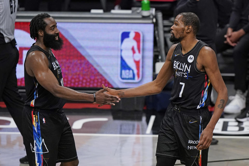 Kevin Durant and James Harden slap hands at the end of their win over the Clippers.