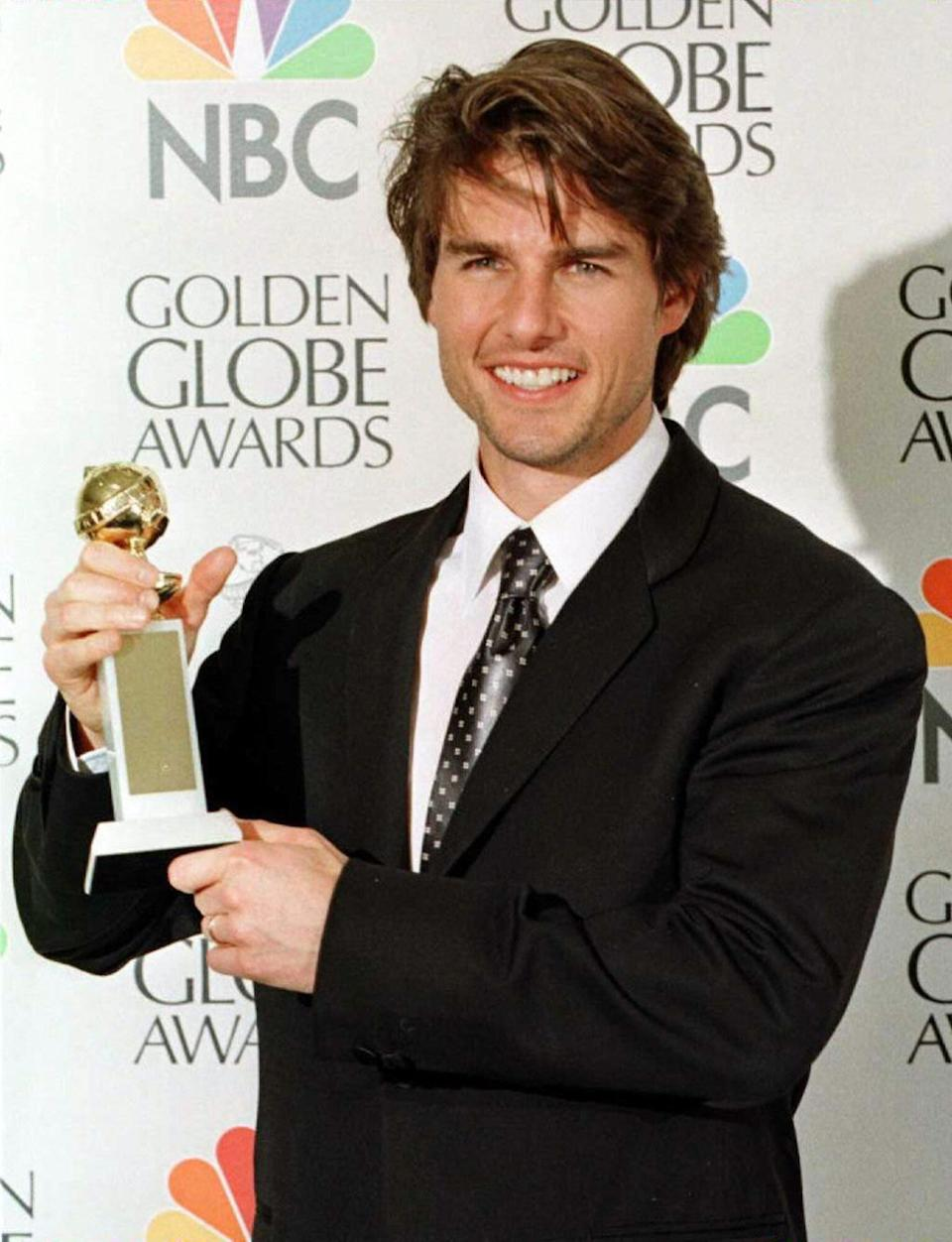 """Tom Cruise holds his award for Best Actor in a Motion Picture Comedy for his role in """"Jerry Maguire"""" 19 January at the 54th Annual Golden Globe Awards"""
