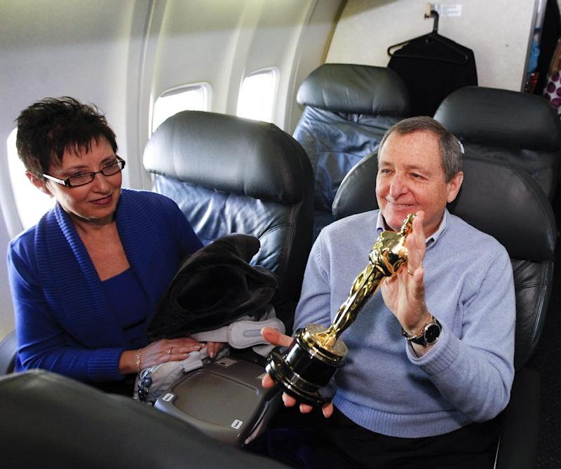 FILE - In this Feb. 9, 2012 file photo, Academy of Motion Picture Arts and Sciences president Tom Sherak, right, and his wife Madeleine pose with a Oscar statue after landing at Los Angeles International Airport as they arrive from Chicago, in Los Angeles. Sherak, a former Academy of Motion Picture Arts and Sciences president, has died of prostate cancer at 68, the Academy confirmed on Tuesday, Jan. 28, 2014. Sherak was surrounded family at his home in Calabasas, Calif. (AP Photo/Chris Carlson, File)