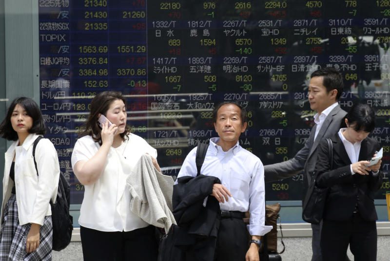 People stand by an electronic stock board of a securities firm in Tokyo, Monday, May 20, 2019. Shares are mixed in Asia, with India and Australia leading gains following elections that look set to keep incumbents in office. (AP Photo/Koji Sasahara)