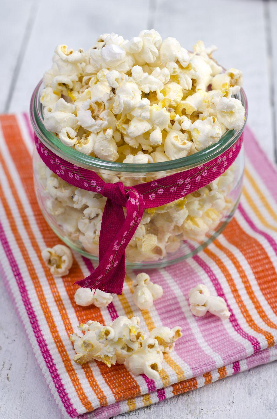 """<p>Full of fiber and light on calories, popcorn is a great snack option. If you're feeling a bit wild, you can punch up your health benefits by eating pop <a href=""""https://www.goodhousekeeping.com/food-recipes/healthy/a37151/cauliflower-popcorn-recipe/"""" rel=""""nofollow noopener"""" target=""""_blank"""" data-ylk=""""slk:caulicorn"""" class=""""link rapid-noclick-resp"""">caulicorn</a>.</p><p>On a cutting board, pile ¼ cup chopped parsley, 1 small clove chopped garlic, ½ teaspoon lemon zest, and 1 tablespoon finely grated Parmigiano Reggiano on top of each other and chop all together until fine. In a large bowl, toss 10 cups air-popped popcorn while spritzing grapeseed oil with a mister. Add the gremolata andand ½ teaspoon salt and toss until coated. Serves 2.</p>"""