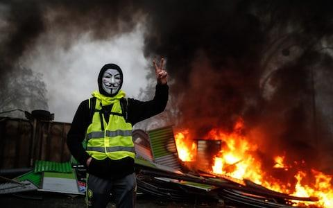 "A protester wearing a Guy Fawkes mask makes the victory sign near a burning barricade during a protest of ""yellow vests"" against rising oil prices and living costs, on December 1, 2018 in Paris. - Credit: ABDULMONAM EASSA/AFP"