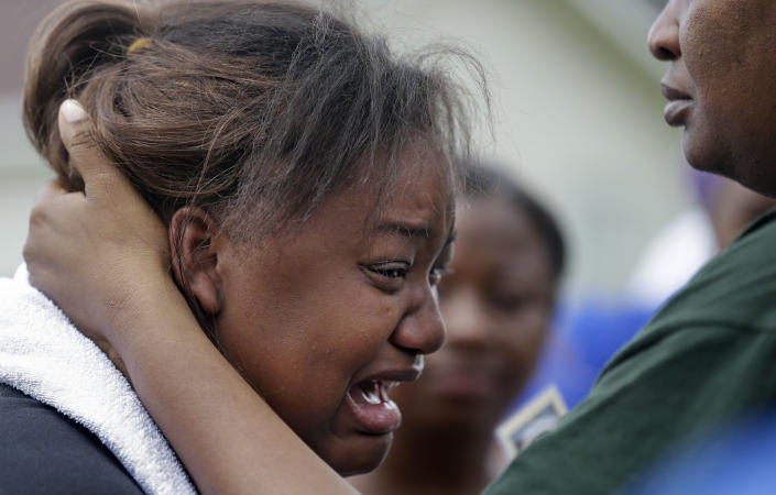 Lisa North, the mother of missing 6-year-old Ahlittia North, cries in the arms of her mother, Rene' Johnson, right, after she says Jefferson Parish authorities have found the body of her daughter in a Harvey trash bin, in Harvey, La., Tuesday, July 16, 2013. Ahlittia disappeared from her apartment late Friday night or early Saturday morning. North's husband Albert Hill said they were told the body was found in a trash bin not far from their apartment. (AP Photo/Gerald Herbert)