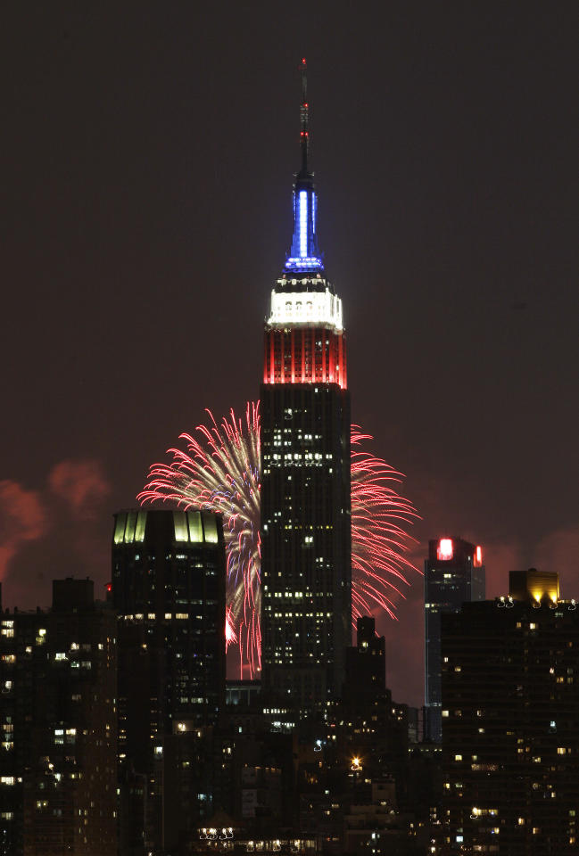 The Empire State Building, illuminated with red, white and blue lights, is seen from the Queens borough of New York, backlit by fireworks lighting up the sky over the Hudson River, during the Macy's Fourth of July fireworks show Wednesday, July 4, 2012, in New York. (AP Photo/Frank Franklin II)