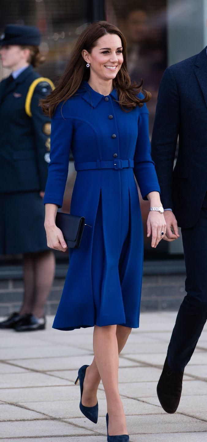 "<p>Kate stepped out in a blue coat dress by <a href=""http://www.eponinelondon.com/aw-16-1"" rel=""nofollow noopener"" target=""_blank"" data-ylk=""slk:Eponine"" class=""link rapid-noclick-resp"">Eponine</a>, which she'd worn <a href=""https://www.townandcountrymag.com/style/fashion-trends/a25058717/kate-middleton-recycle-eponine-cota-dress-south-yorkshire-photos/"" rel=""nofollow noopener"" target=""_blank"" data-ylk=""slk:once before in 2017."" class=""link rapid-noclick-resp"">once before in 2017.</a> The Duchess styled her outfit with navy stilettos from <a href=""https://www.net-a-porter.com/us/en/Shop/Designers/Rupert_Sanderson?cm_mmc=LinkshareUS-_-tv2R4u9rImY-_-Custom-_-LinkBuilder&siteID=tv2R4u9rImY-JoE9OpvJZ9WOW.hrlHo8Xg&Skimlinks+%28Variable+Pricing%29=Skimlinks+%28Variable+Pricing%29&dclid=CjkKEQiArK_fBRCn8-rxz42j3bgBEiQAFHPBMEbPaYejrHq0Xs3_Sz8r2pLWKoU7GOw8bgTZz37EIhvw_wcB&pn=1&npp=60&image_view=product&dScroll=0"" rel=""nofollow noopener"" target=""_blank"" data-ylk=""slk:Rupert Sanderson"" class=""link rapid-noclick-resp"">Rupert Sanderson</a>, sapphire drop earrings, and a black clutch. </p>"