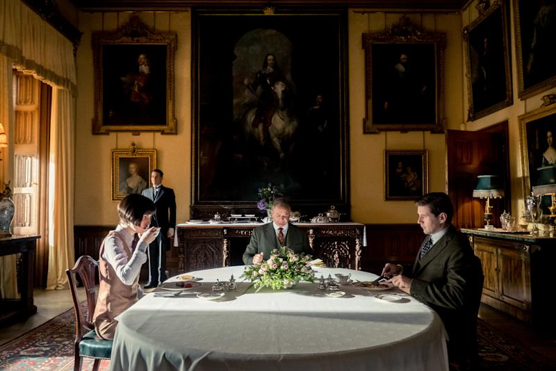 michelle dockery, hugh bonneville and allen leech sitting at a breakfast table on the set of the new downton abbey movie