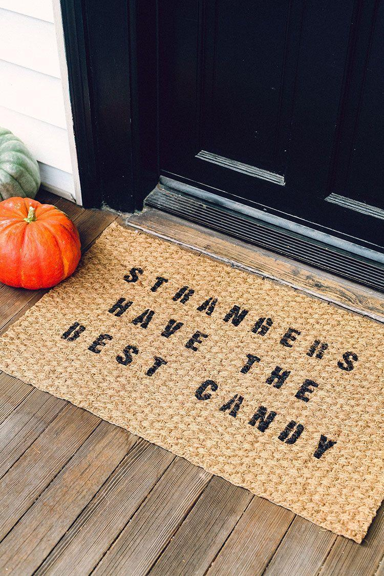 """<p>""""Strangers have the best candy,"""" reads this funny doormat—but of course, you can change up the message to say just about whatever you want. The best part is that the mat itself can be reused every year.</p><p><strong>Get the tutorial at <a href=""""https://jojotastic.com/2016/10/12/diy-halloween-themed-door-mat-for-less-than-10/"""" rel=""""nofollow noopener"""" target=""""_blank"""" data-ylk=""""slk:jojotastic"""" class=""""link rapid-noclick-resp"""">jojotastic</a>. </strong></p><p><a class=""""link rapid-noclick-resp"""" href=""""https://go.redirectingat.com?id=74968X1596630&url=https%3A%2F%2Fwww.walmart.com%2Fip%2FTestors-Craft-Acrylic-Paint%2F49019888%3FvariantFieldId%3Dactual_color&sref=https%3A%2F%2Fwww.thepioneerwoman.com%2Fholidays-celebrations%2Fg32894423%2Foutdoor-halloween-decorations%2F"""" rel=""""nofollow noopener"""" target=""""_blank"""" data-ylk=""""slk:SHOP BLACK PAINT"""">SHOP BLACK PAINT</a><br></p>"""