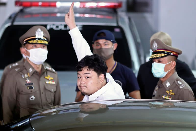 Parit Chiwarak is escorted after being arrested at the police station in Bangkok