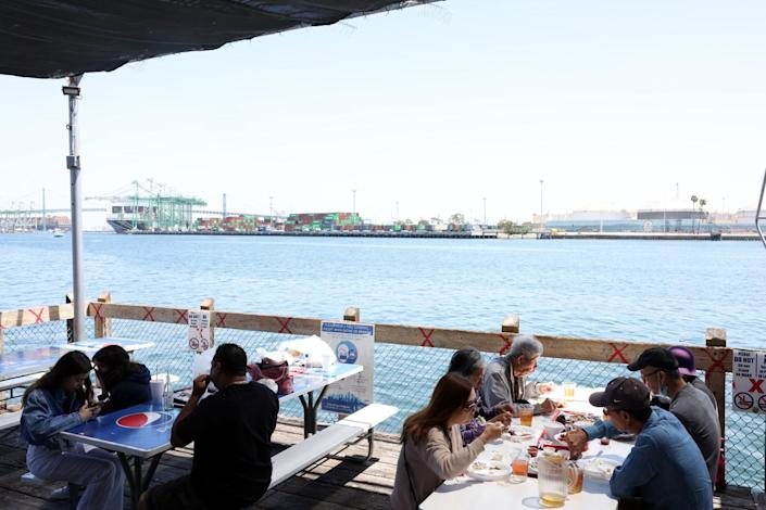 People eat outside on the dock at the San Pedro Fish Market