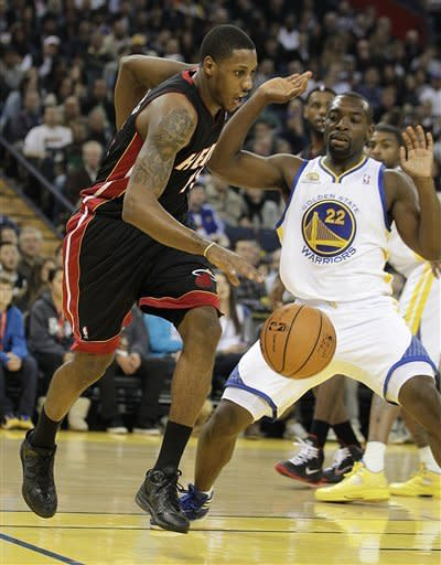 Miami Heat's Mario Chalmers, left, drives the ball past Golden State Warriors' Charles Jenkins (22) during the first half of an NBA basketball game, Tuesday, Jan. 10, 2012, in Oakland, Calif. (AP Photo/Ben Margot)