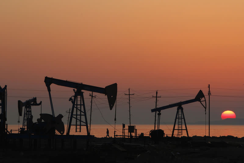 Pump jacks are silhouetted against the rising sun on an oilfield in Baku