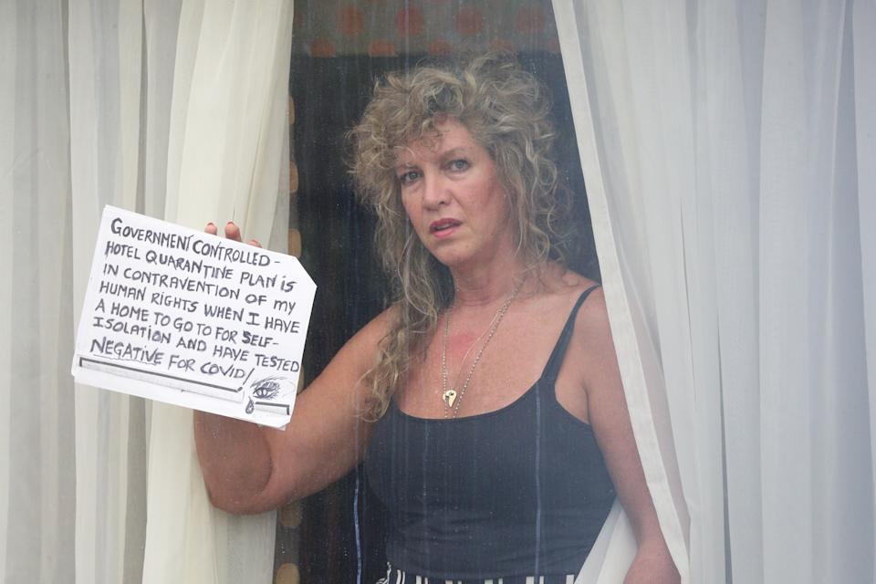 A quarantined traveller holds a sign up to the window of her room at the Radisson Blu Edwardian hotel, near Heathrow Airport, London, a Government-designated quarantine hotel being used for travellers to stay during a 10-day quarantine after returning to England from one of 33