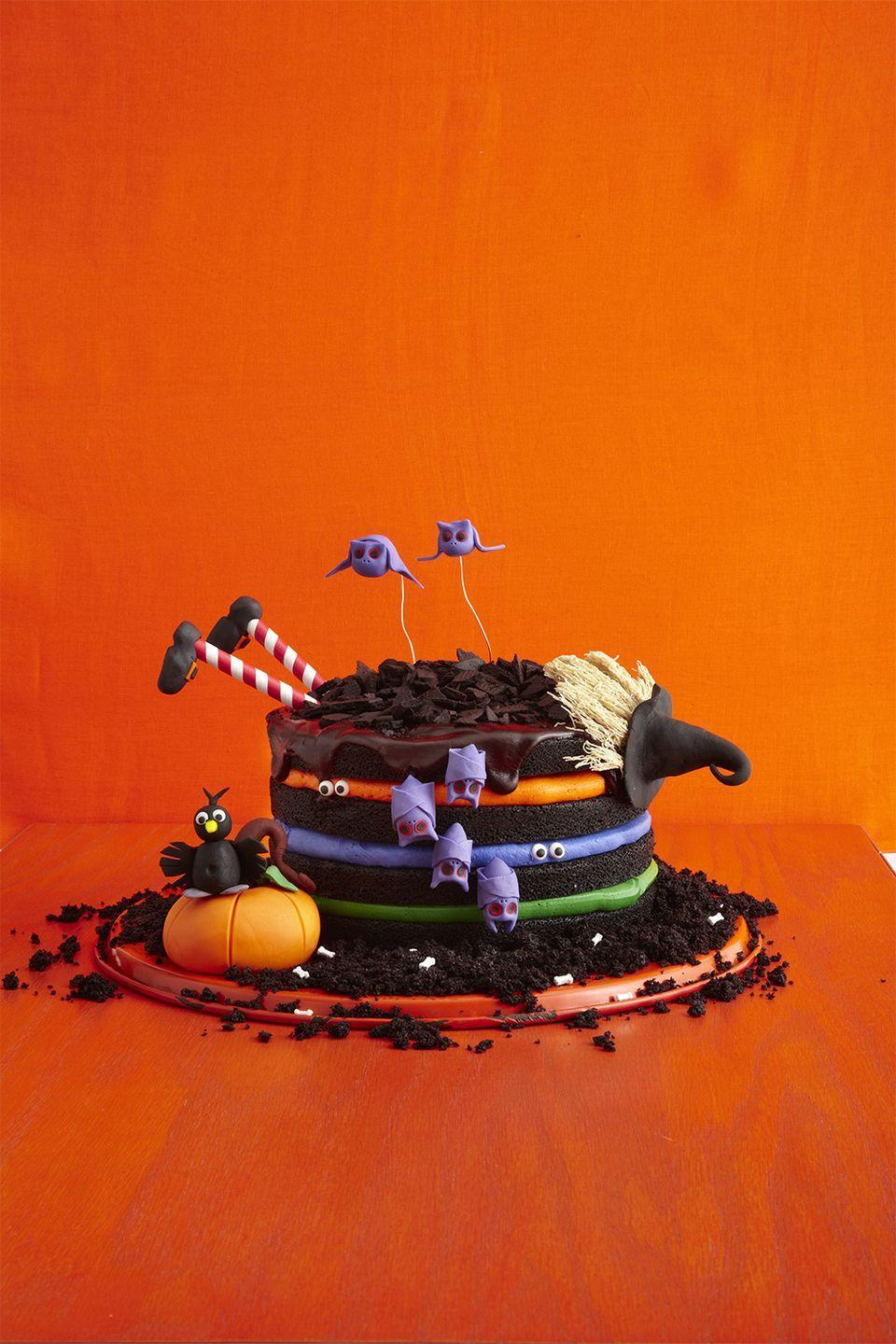 """<p>Can you blame the witch for flying into a cake this delicious? Homemade buttercream frosting and spooky decorations just add to the fun.</p><p><em><a href=""""https://www.womansday.com/food-recipes/food-drinks/recipes/a51843/black-chocolate-cake/"""" rel=""""nofollow noopener"""" target=""""_blank"""" data-ylk=""""slk:Get the Black Chocolate Witch Cake recipe."""" class=""""link rapid-noclick-resp"""">Get the Black Chocolate Witch Cake recipe.</a></em></p>"""