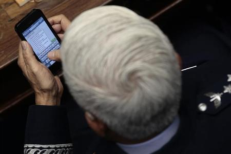 Brazilian Air Force Commander, Lieutenant-Brigadier Juniti Saito, writes a text message to an unidentified person named Araujo to celebrate the government's decision to purchase fighter aircraft from Sweden's Saab, as he attended a ceremony at the National Congress in Brasilia, December 18, 2013. REUTERS/Ueslei Marcelino