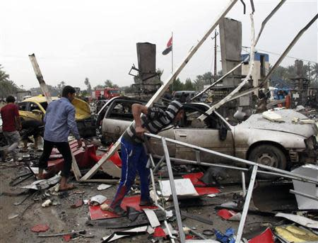 People look at the damage and wreckage at the site of a suicide attack in the city of Hilla