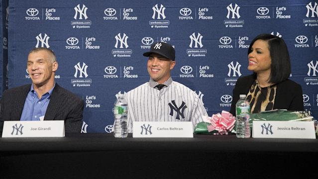 Carlos Beltran, center, smiles alongside his wife Jessica, right, and New York Yankees manager Joe Girardi, left, during a news conference at Yankees Stadium, Friday, Dec. 20, 2013, in New York. The former St. Louis Cardinals outfielder signed with the New York Yankees on a $45 million, three-year contract.(AP Photo/John Minchillo)
