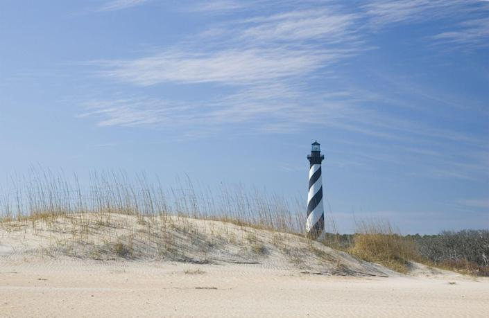 <p>Nestled in North Carolina's Outer Banks, the striped Hatteras Lighthouse has been standing above the dunes since 1870. </p>