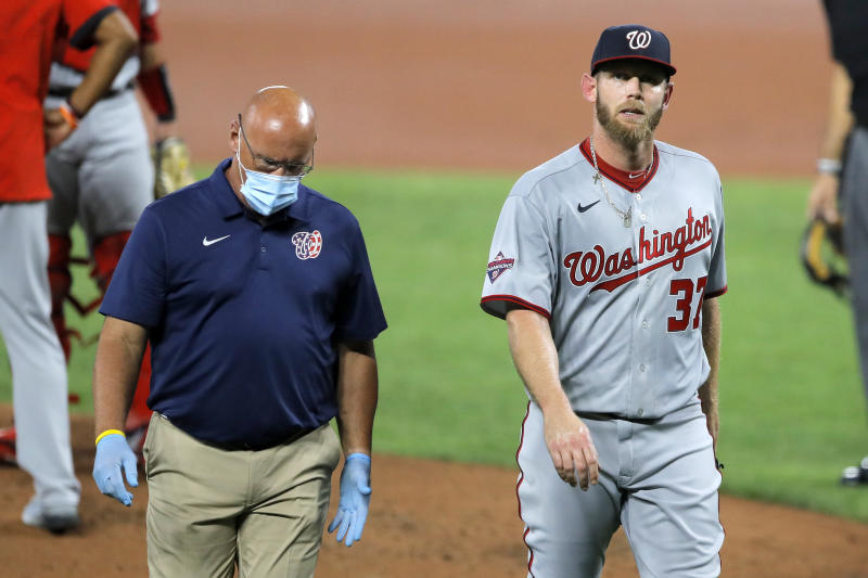 Washington Nationals starting pitcher Stephen Strasburg, right, walks with a member of the training staff as he heads to the dugout after leaving the game during the first inning of a baseball game against the Baltimore Orioles, Friday, Aug. 14, 2020, in Baltimore. (AP Photo/Julio Cortez)