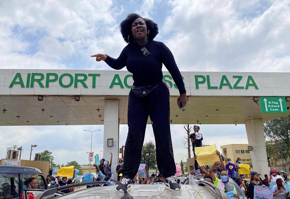 A demonstrator stands atop a vehicle and shouts slogans as others carry banners while blocking a road leading to the airport in Lagos on Oct. 12, 2020.