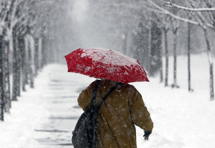 A woman walks through a snow covered street in Belgrade, Serbia, Sunday, Jan. 17, 2021. Meteorologists predict sub zero temperatures in Serbia throughout the coming week. (AP Photo/Darko Vojinovic)