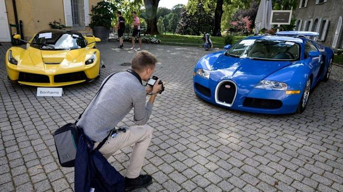 A picture taken on September 28, 2019 at the Bonmont Abbey in Cheserex, western Switzerland shows a 2015 Ferrari LaFerrari (L) and a 2010 Bugatti Veyron EB 16.4 Coupe model car during an auction preview by sales house Bonhams of sport cars belonging to the son of the Equatorial Guinea's President