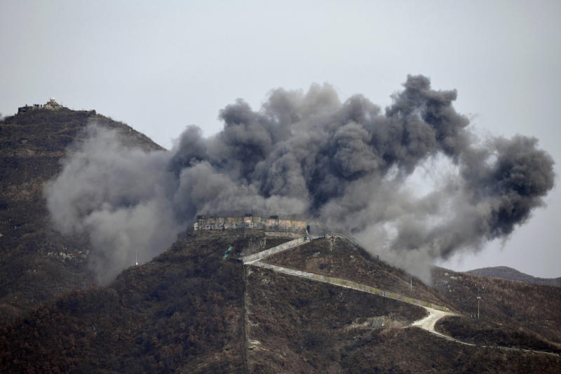 FILE - In this Nov. 15, 2018, file photo, smoke from an explosion rises as part of the dismantling of a South Korean guard post in the Demilitarized Zone dividing the two Koreas in Cheorwon, South Korea, as a North Korean guard post sits high in the upper left. President Donald Trump is inviting North Korea's Kim Jong Un to shake hands during a visit to the demilitarized zone with South Korea. Trump is scheduled to visit South Korea later Saturday after meetings at the Group of 20 summit in Osaka, Japan. (Jung Yeon-je/Pool Photo via AP, File)