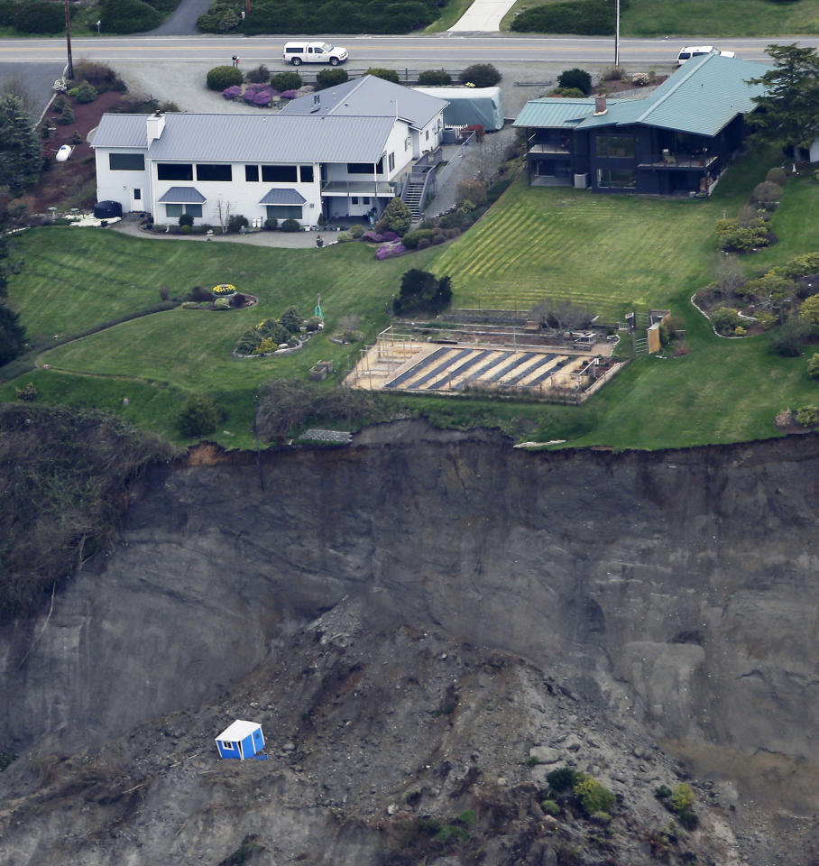 In this aerial photo, a house sits near the edge of a landslide, near Coupeville, Wash. on Whidbey Island, Wednesday, March 27, 2013. The slide severely damaged one home and isolated or threatened more than 30 on the island, about 50 miles north of Seattle in Puget Sound. No one was reported injured in the slide, which happened at about 4 a.m. Wednesday. (AP Photo/Ted S. Warren)