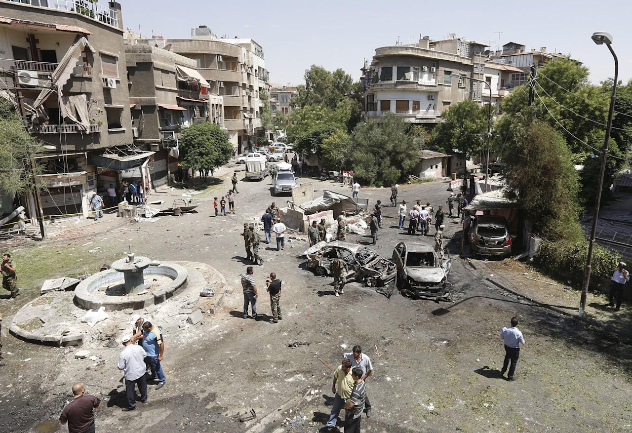 <p>Syrians gather to inspect the damage at the site of a suicide bomb attack in the capital Damascus' eastern Tahrir Square district, on July 2, 2017. (Louai Beshara/AFP/Getty Images) </p>