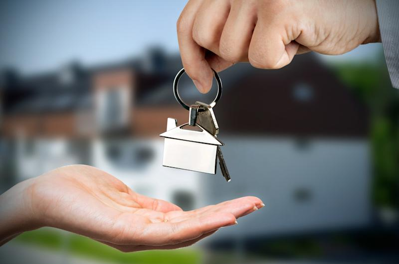 A person giving house keys to another person
