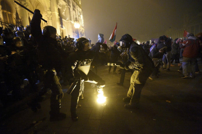 """Protesters clash with police during a demonstration against the amendments to the labour code, dubbed """"slave law"""" by oppositional forces, at the parliament building in Budapest, Hungary, Dec. 13, 2018. The rally, which was announced by the Free University and Students Trade Union student groups, started peacefully but police later responded to aggressive protestors with teargas. (Zoltan Balogh/MTI via AP)"""