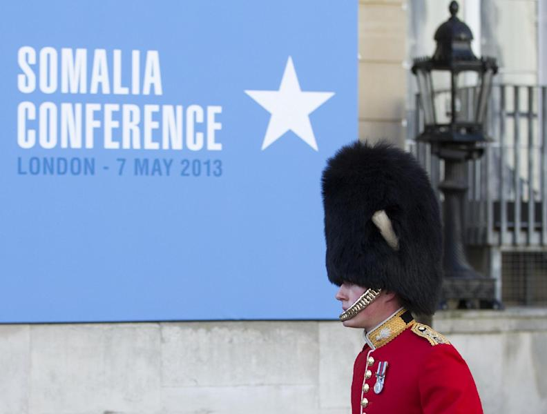 A member of the Grenadier Guards walks past a sign outside the Somalia Conference held at Lancaster House in London, Tuesday May 7, 2013. British Prime Minister David Cameron is welcoming Somalia's president and a host of international leaders to London for a conference aimed at securing support for the government in Mogadishu after two decades of conflict. (AP Photo/Alastair Grant)