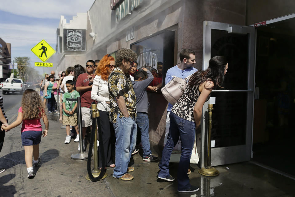 In this Wednesday, April 3, 2013, photo, customers wait in a line that stretches down the block to enter the Gold and Silver Pawn Shop, in Las Vegas. Pawn sales at the shop, which is featured in the television reality show Pawn Stars, bring in about $20 million a year, up from the $4 million a year it made before the show aired. Turning small business owners into stars has become a winning formula for television producers, but the businesses featured in the shows are cashing in, too. Sales explode after just a few episodes have aired, transforming nearly unknown small businesses into household names. (AP Photo/Julie Jacobson)