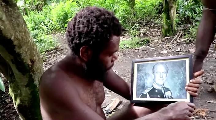 A man holds a picture of Britain's Prince Philip as late Duke's devotees hold a mourning ceremony in his honour on the island of Tanna in Vanuatu in this screengrab taken from a video on April 12, 2021. REUTERS TV via REUTERS