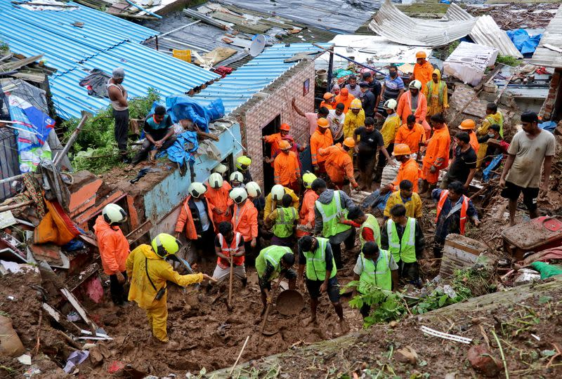 Rescue workers search for survivors after a residential house collapsed due to landslide caused by heavy rainfall in Mumbai