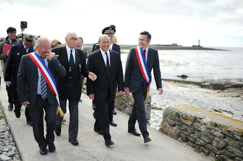French Defence Minister Jean-Yves Le Drian (C) flanked by Colonel Fred Moore (2ndL), a French veteran and Compagnon de la Liberation, leads a ceremony to pay homage to the Force Fran�aise Libres (Free French forces) who fought the nazis during the second world war on August 30, 2013 at the Ile-de-Sein (Sein Island), western France. AFP PHOTO / JEAN-SEBASTIEN EVRARD / AFP PHOTO / JEAN-SEBASTIEN EVRARD