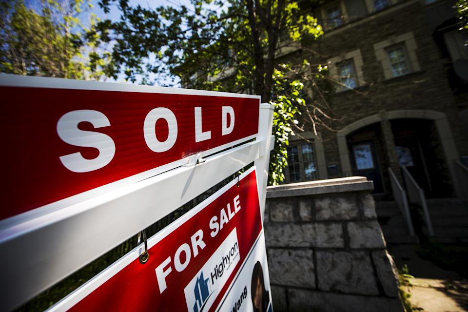 """A """"For Sale"""" sign stands in front of a home that has been sold in Toronto"""
