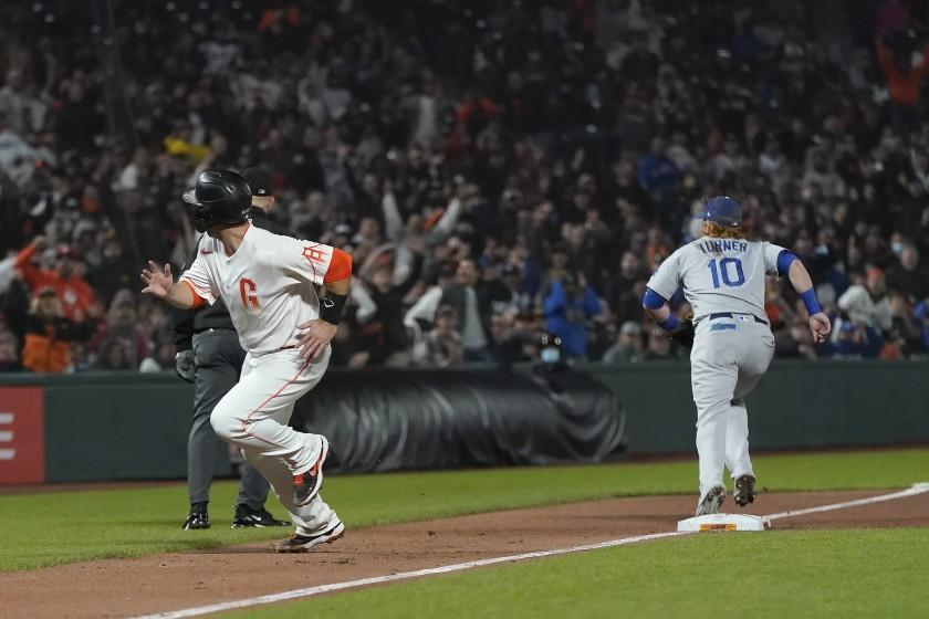 San Francisco Giants' Buster Posey, left, runs home to score as Dodgers third baseman Justin Turner (10) looks for the ball