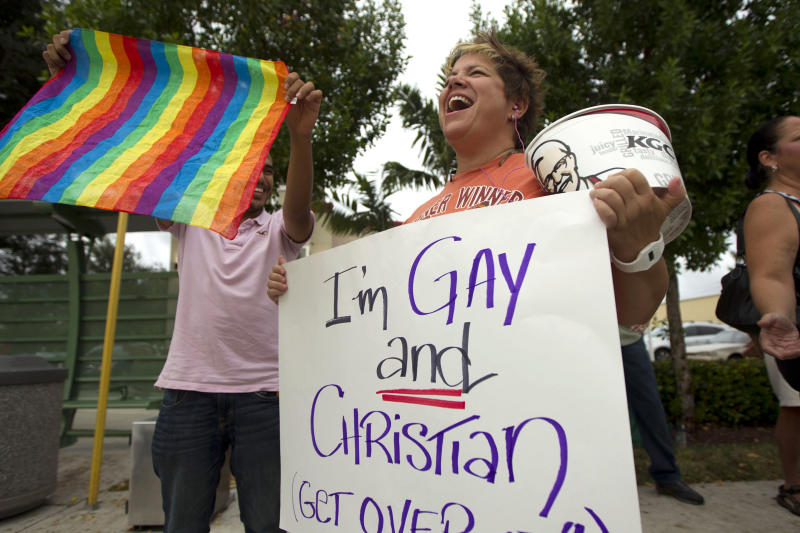 FILE - In a Friday, Aug. 3, 2012 file photo, Carri Jo Anderson holds a bucket of Kuntucky Fried Chicken and a gay pride sign as she joins the protest in front of a Chick-fil-A restaurant in Pompano Beach, Fla. Gay rights activists kissed at Chick-fil-A stores across the U.S. on Friday, just days after the company set a sales record when customers flocked to the restaurants to show support for the fast-food chain president's opposition to gay marriage. On this and so many other issues this election year, it seems harder to find that middle-ground gray when our debates seem so very black or white. (AP Photo/J Pat Carter, File)