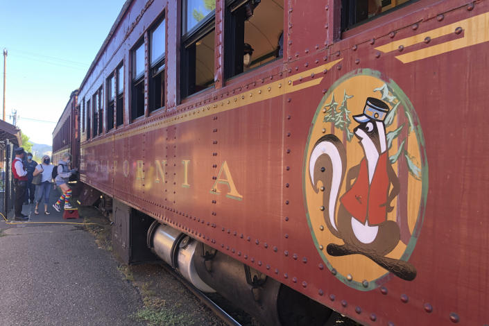 """People board the Skunk Train in Willits, Calif., Wednesday, Aug. 4, 2021. Tourists flock to the picturesque coastal town of Mendocino for its Victorian homes and cliff trails, but visitors this summer will also find public portable toilets and dozens of signs on picket fences announcing the quaint Northern California hamlet: """"Severe Drought Please conserve water."""" Robert Pinoli, president of Mendocino Railway, which operates the Skunk Train, said he is ready to help. The excursion train has been running from Willits through redwood forests and river canyons to Fort Bragg since 1885, when it was built to transport timber. Pinoli said he could find tank cars quickly and attach them to the locomotive and could deliver up to 200,000 gallons each trip. (AP Photo/Haven Daley)"""