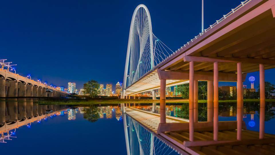 Night lights fill the sky and reflect in the water under the bridge in Dallas, Texas.