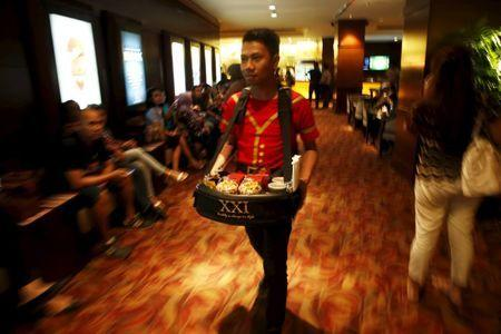 An employee of Cinema 21 Group carries snack and drinks to sell inside a theater at Djakarta Theater in Jakarta, Indonesia, February 18, 2016. REUTERS/Beawiharta