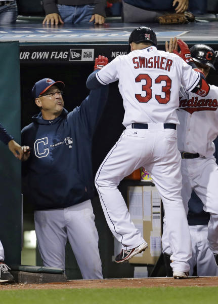 Cleveland Indians manager Terry Francona, left, slaps hands with Nick Swisher after Swisher hit a two-run home run off Chicago White Sox starting pitcher Dylan Axelrod in the fifth inning of a baseball game, Wednesday, Sept. 25, 2013, in Cleveland. (AP Photo/Tony Dejak)