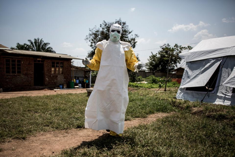 TOPSHOT - A health worker gets ready to perform medical checks inside an Ebola Treatment Centre run by The Alliance for International Medical Action (ALIMA) on August 11, 2018, in Beni. (Photo by John WESSELS / AFP) (Photo by JOHN WESSELS/AFP via Getty Images)
