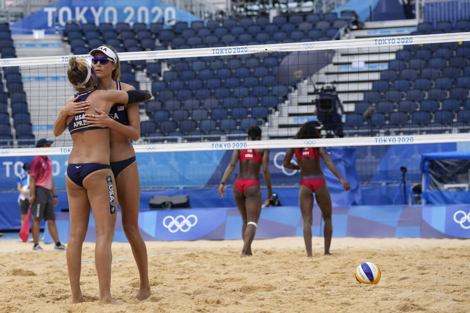 April Ross, left, of the United States, hugs teammate Alix Klineman during a women's beach volleyball match against Cuba at the 2020 Summer Olympics, Monday, Aug. 2, 2021, in Tokyo, Japan. (AP Photo/Petros Giannakouris)