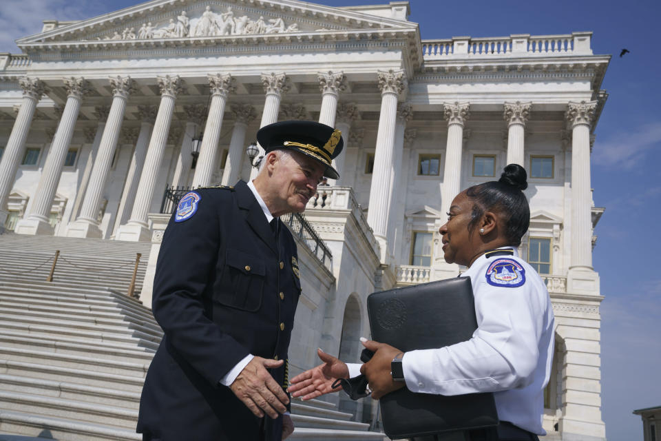 FILE - In this July 23, 2021, file photo J. Thomas Manger, left, a veteran police chief of departments in the Washington, D.C., region, is welcomed by interim acting Capitol Police chief Yogananda Pittman, to the Capitol in Washington as he takes over the United States Capitol Police following the resignations of the previous leadership after the Jan. 6 insurrection. Pittman, the Capitol Police official who led intelligence operations when thousands of pro-Trump rioters descended Jan. 6, is back in charge of intelligence as officials prepare for what's expected to be a massive rally at the Capitol to support those who took part in the insurrection. Pittman has been put back in charge as assistant chief of the agency's intelligence operations and supervising officers who protect top congressional leaders. (AP Photo/J. Scott Applewhite, File)
